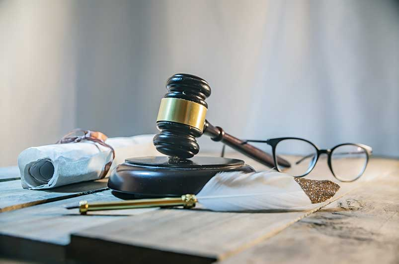 gavel on table with papers and other instruments